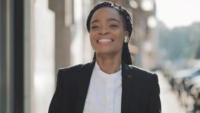耳机的年轻愉快的非裔美国人的女实业家走城市街道的,当听到在时的音乐 股票录像