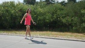 耳机的年轻深色的女孩走通过公园的 桃红色顶面微笑和跳舞的嬉戏女孩在公园 有吸引力的妇女锂 影视素材