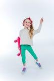 耳机的微笑的女孩有在灰色的滑板听的音乐的 免版税库存照片