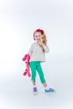 耳机的微笑的女孩有在灰色的滑板听的音乐的 免版税库存图片