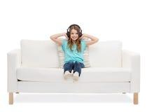 耳机的微笑的小女孩坐沙发 免版税库存照片