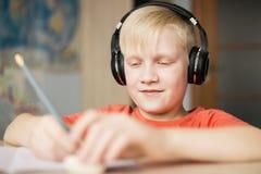 耳机的微笑的男孩写和 图库摄影