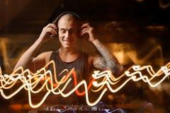 耳机的微笑的DJ在夜总会背景点燃 库存照片
