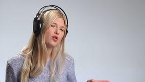 耳机的情感年轻金发碧眼的女人在白色 股票视频
