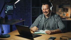 耳机的愉快的办公室工作者听到音乐的繁忙与膝上型计算机在晚上 影视素材