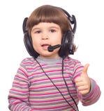 耳机的愉快的小女孩有话筒的显示标志ok 图库摄影