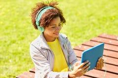 耳机的愉快的非洲妇女有片剂个人计算机的 免版税库存图片