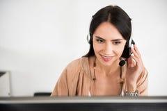 耳机的感兴趣的微笑的女性雇员 免版税库存图片