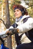 耳机的欧洲可爱的妇女在的秋天森林里 免版税库存照片