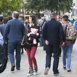 耳机的深色的女孩,在红色牛仔裤,皮夹克拿着趟过通过人群的一个桃红色玩具熊 库存图片