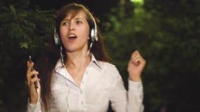 耳机的给听音乐跳舞打电话微笑在夜城市的女孩和接触在灯笼下光  股票录像