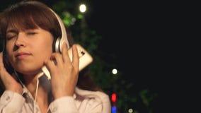 耳机的给跳舞打电话微笑和享受音乐的女孩有长的头发的和接触在公园在晚上 特写镜头 影视素材