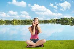 耳机的美丽的女孩听到音乐在河附近 免版税库存图片