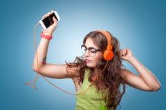 耳机的美丽的女孩听音乐和跳舞的 免版税库存照片