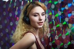 耳机的美丽的妇女获得乐趣并且听音乐 免版税库存图片