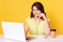 耳机的美丽的年轻深色头发的女孩有话筒的在与膝上型计算机的桌上,运转坐键盘和谈话与 免版税图库摄影