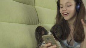 耳机的美丽的青少年的女孩唱在智能手机的卡拉OK演唱歌曲有狗股票英尺长度录影的 股票录像