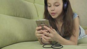 耳机的美丽的青少年的女孩唱在智能手机股票英尺长度录影的卡拉OK演唱歌曲 股票录像