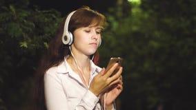 耳机的美女听到在她的智能手机和舞蹈的音乐 女孩在晚上走在城市公园由 股票视频
