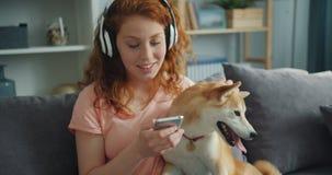耳机的美女听音乐和爱犬的在长沙发 股票视频