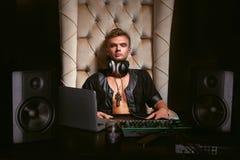 耳机的英俊的年轻快乐音乐家DJ 免版税库存图片
