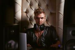 耳机的英俊的年轻快乐音乐家DJ 图库摄影