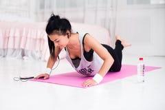 耳机的适合的运动的妇女做俯卧撑在家训练听的音乐的在智能手机概念crossfit健身 图库摄影