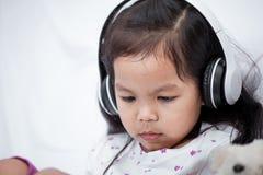 耳机的逗人喜爱的亚裔小孩女孩使用一种片剂 免版税库存照片