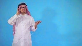 耳机的阿拉伯人听到音乐的站立在蓝色背景 股票录像