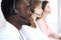 耳机的非裔美国人的电话操作员 电话中心事务或顾客服务概念 免版税库存图片