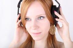 耳机红头发人年轻人 库存图片
