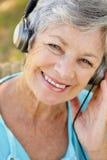 耳机高级微笑的妇女 免版税库存图片