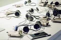 耳机,耳机,电话在桌上 免版税库存图片