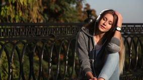 耳机 放松美丽的女孩和在城市公园听在耳机的音乐 耳机的妇女 股票录像