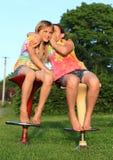 耳语两个的女孩,当坐酒吧椅子时 免版税库存照片