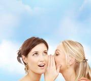 耳语两名微笑的妇女闲话 库存图片