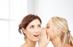耳语两名微笑的妇女闲话 免版税图库摄影