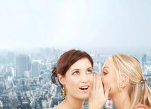 耳语两名微笑的妇女闲话 免版税库存图片