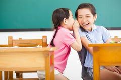 耳语和分享一个秘密的小女孩在教室 免版税库存照片