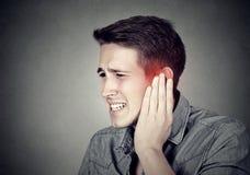 耳鸣 有病的人接触他痛苦的头的耳痛 免版税库存图片