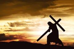 耶稣剪影运载他的十字架 免版税库存图片