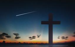 耶稣受难象十字架和夜空剪影在日落时间的有流星背景 库存图片