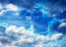 耶稣受难象或十字架形式发光在松的云彩蓝天的,天堂 免版税库存照片