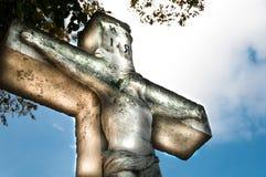 耶稣基督在十字架上钉死在天空背景和自然光的耶稣基督雕象 库存照片