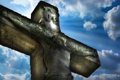 耶稣基督在十字架上钉死在天空背景和自然光的耶稣基督雕象 免版税库存图片