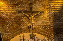 耶稣基督在十字架上钉死雕象在砖墙背景的 免版税库存图片