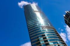 耸立入与蓬松蓝色云彩和太阳火光的蓝天的现代天空刮板反射在它的弯曲的门面的周围的builings 库存照片