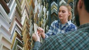 聊天与关于画框细节的顾客的男性工作者在工作室 库存照片