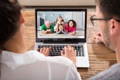 聊天与在膝上型计算机的家庭的夫妇 免版税图库摄影