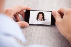 聊天与女性同事的商人通过智能手机 图库摄影